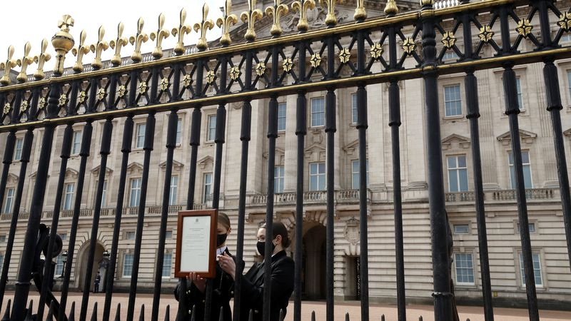 The Union flag hangs at half staff as members of staff attach an announcement, regarding the...