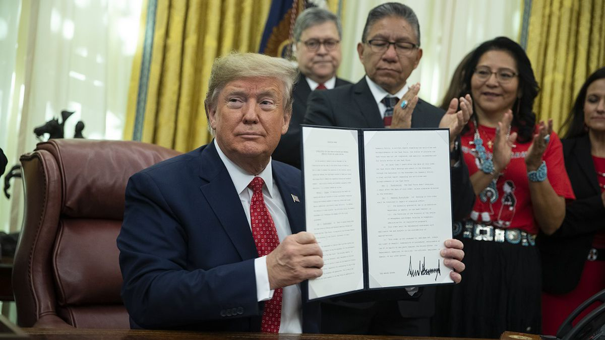 President Donald Trump shows an executive order establishing the Task Force on Missing and Murdered American Indians and Alaska Natives, in the Oval Office of the White House, Tuesday, Nov. 26, 2019, in Washington. (AP Photo/ Evan Vucci)