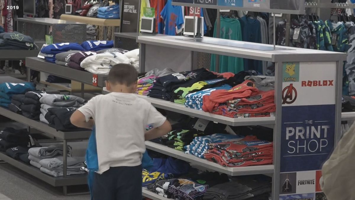A young boy is picking out an outfit at Kohls.