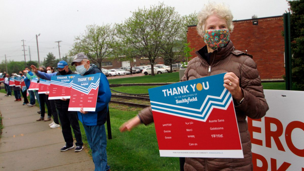 Sioux Falls resident Pat Lloyd, right, waves to greet employees of a Smithfield pork processing plant as they begin their shift on Wednesday, May 20, 2020, in Sioux Falls, S.D. Smithfield called many employees back to work after it closed the plant for more than three weeks because of a coronavirus outbreak that infected over 800 employees. (AP Photo/Stephen Groves)