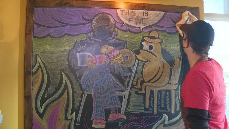Dan Lutz of Rapid City starts to wipe away a colorful depiction of Senator Bernie Sanders in...