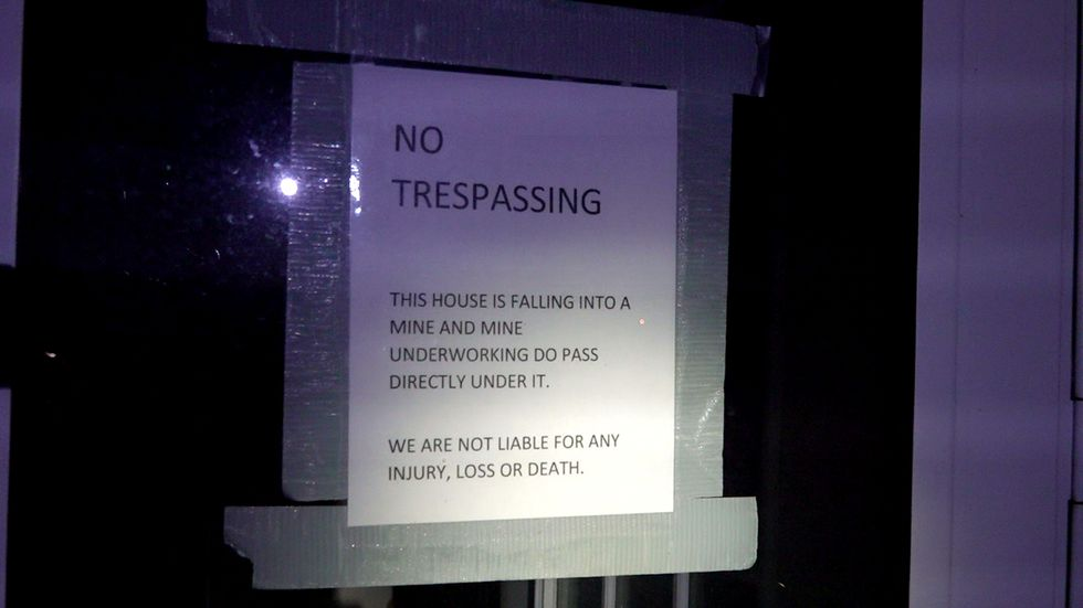 """A sheet of paper taped to a window reading """"NO TRESPASSING"""" warns the reader from entering one..."""