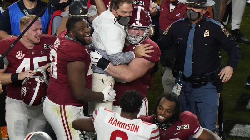 Players celebrate with Alabama head coach Nick Saban after their win against Ohio State in an...