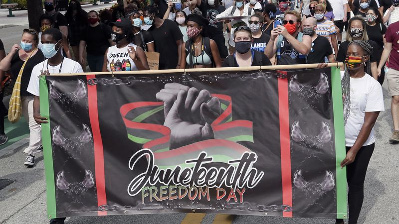 FILE - In this June 19, 2020, file photo, demonstrators march through downtown Orlando, Fla.,...