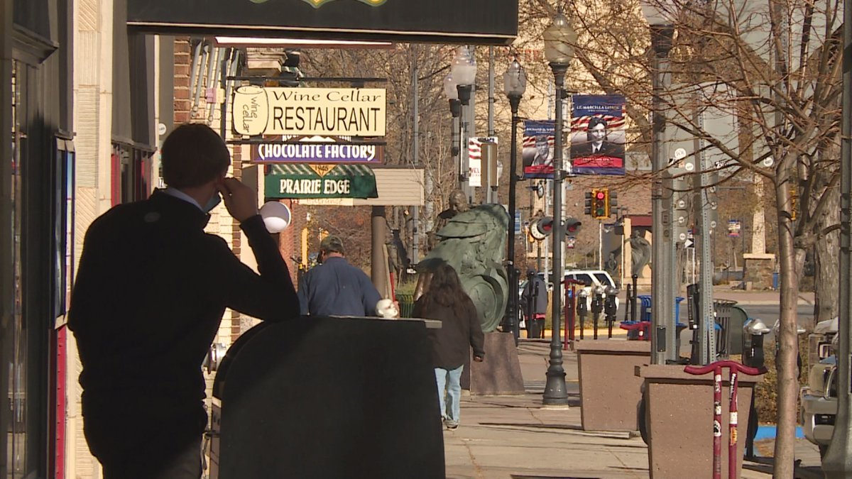 A doorman looks on as pedestrians browse storefronts along Rapid City's 6th Street on Tuesday,...