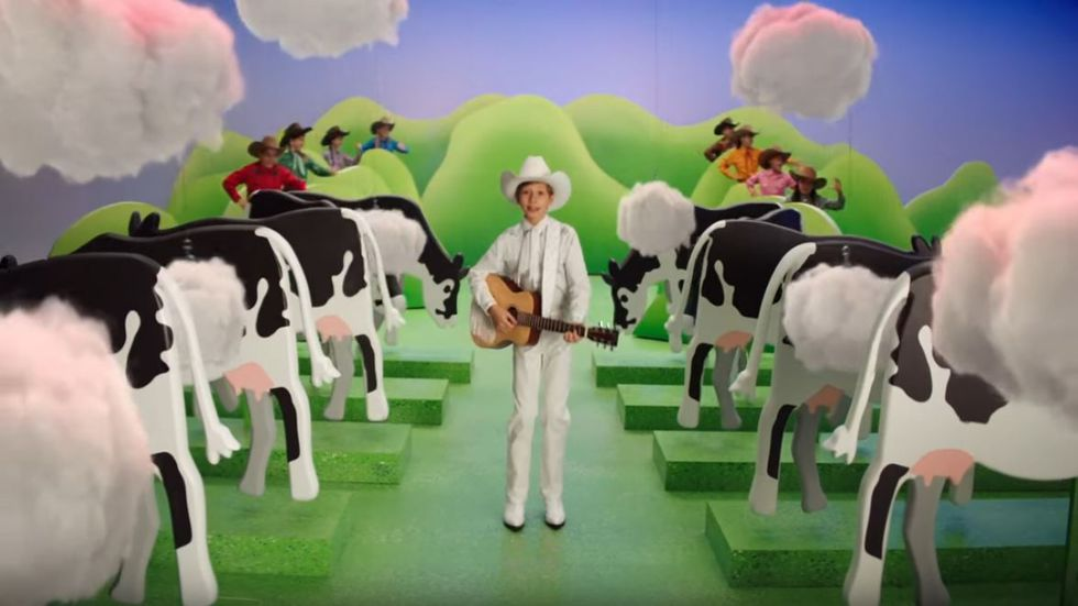 """Walmart yodeler"" Mason Ramsey walks through a cartoonish pasture while flanked by farting dairy cows. Ag industry leaders criticized Burger King over inaccurate depictions of basic bovine biology in their latest ""Cow's Menu"" campaign, which aims to reduce methane emissions from livestock."