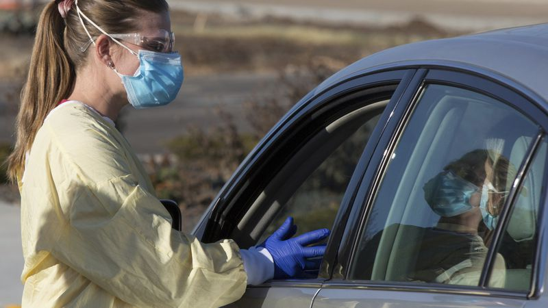 Physician assistant Nicole Thomas conducts a COVID-19 examination in the parking lot at Primary...