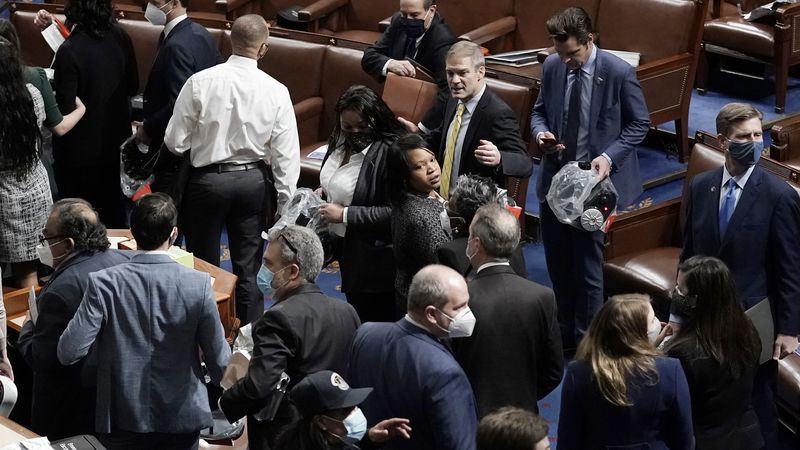 House of Representatives members leave the floor of the House chamber as protesters try to...
