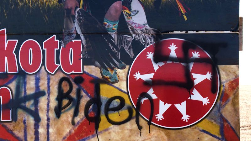 """A drawing likely intended to be a swastika and the word """"Biden"""" partially cover the Oglala..."""